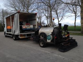 vrachtauto met sproeiunit en strooier